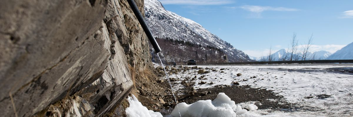 Water streams from a pipe stuck in a drainage hole in rock along the Seward Highway at Mile 109 on March 20, 2017. (Marc Lester / ADN archive)