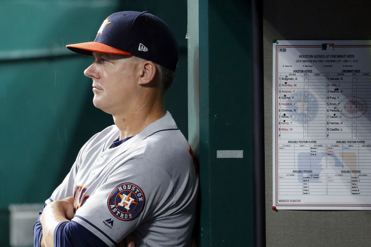 "FILE - In this June 17, 2019, file photo, Houston Astros manager AJ Hinch looks on from the dugout in the fifth inning of a baseball game against the Cincinnati Reds in Cincinnati. The AL champions have been dogged by allegations of spying, most recently during this year's ALCS against the Yankees. Houston players were suspected of whistling in the dugout to communicate pitch selection to batters, an allegation manager AJ Hinch called ""ridiculous."" (AP Photo/John Minchillo, File)"