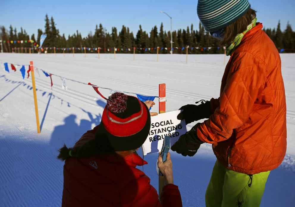 Jen Jolliff and Springer Moore post a note reminding participants to social distance. (Emily Mesner / ADN)