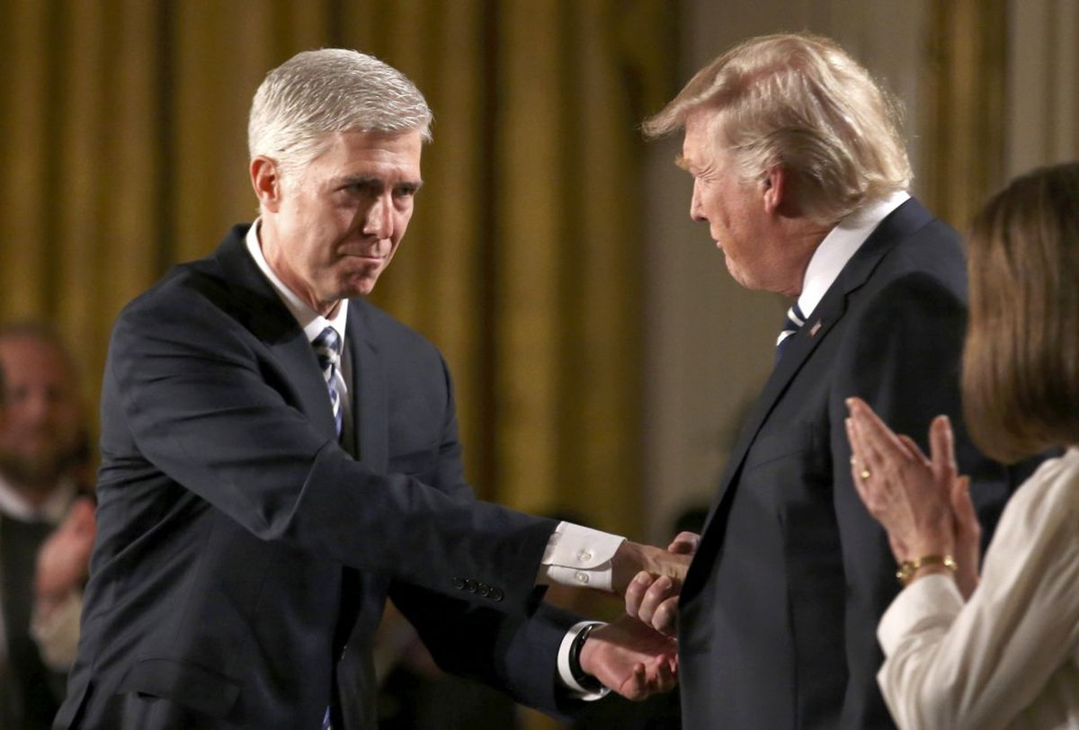 Judge Neil Gorsuch shakes hands with President Donald Trump as Gorsuch's wife, Louise, applauds after President Trump nominated Gorsuch to the U.S. Supreme Court on Tuesday, Jan. 31, 2017, at the White House. (Carlos Barria / REUTERS)