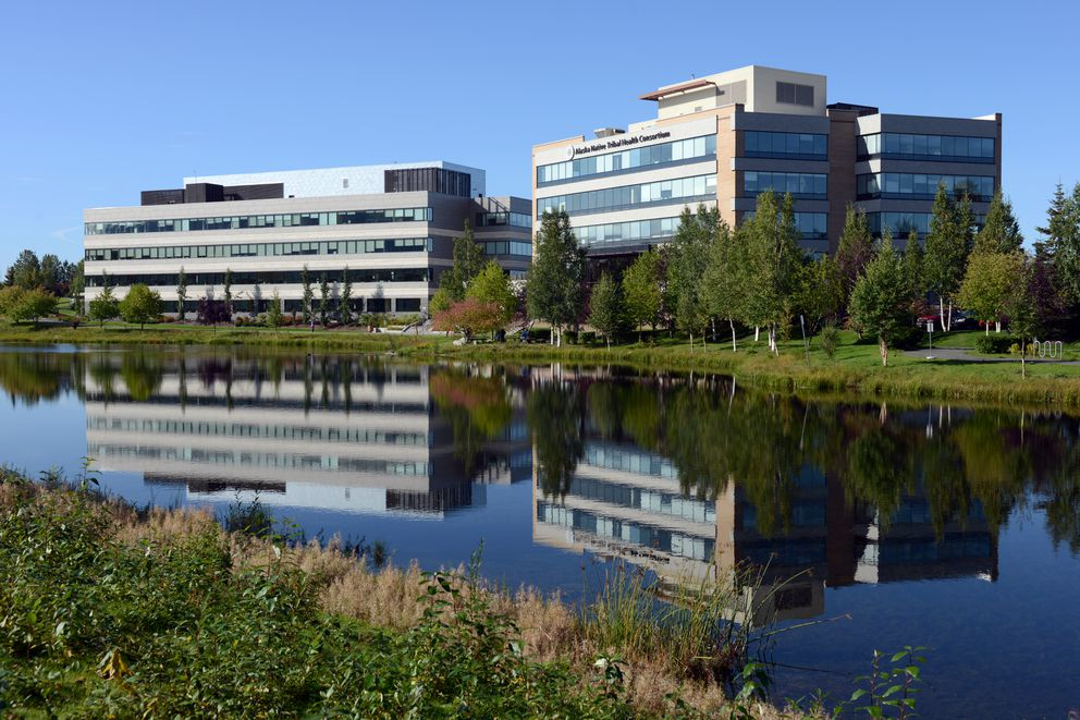The Alaska Native Tribal Health Consortium office building, right, and the connected ANTHC Healthy Communities Building are reflected in the neighboring lake on the Alaska Native Health Campus. (Erik Hill / Alaska Dispatch News)