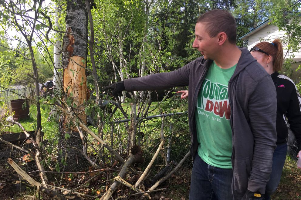 Homeowner David Dirkes points to damage caused when a man allegedly crashed a stolen vehicle early Saturday, May 26, 2018, at the corner of Upper and Lower Sunny Circle in Eagle River. On Saturday afternoon, Brock Werder, 20, was arraigned on stolen vehicle charges related to the incident. (Matt Tunseth / Alaska Star)