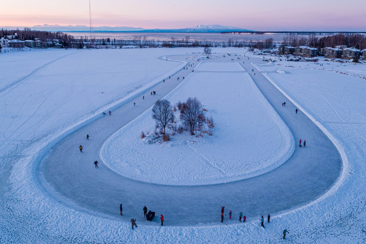People ice skate on a track at Westchester Lagoon on Dec. 31, 2020. (Loren Holmes / ADN)