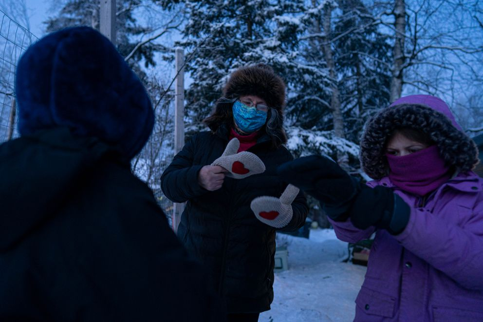 Levesque offers a mitten to a student who lost one before class. (Loren Holmes / ADN)