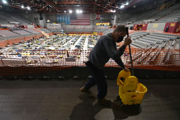 Volunteer Charles Haught mopped around mats used for overflow at the homeless shelter in the Sullivan Arena on Wednesday evening, Oct. 14, 2020. (Bill Roth / ADN)