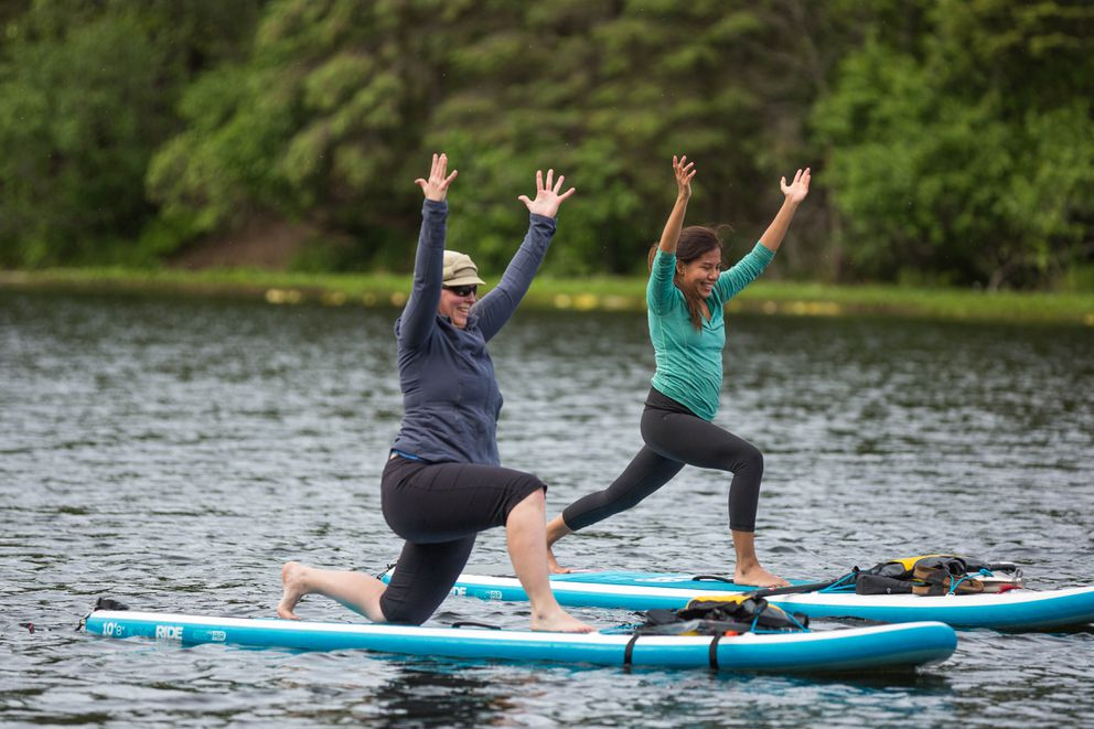 Katriina Timm, left, and Christine Adams participate in a paddleboard yoga class with Alaska Wilderness SUP at Little Campbell Lake on Saturday, June 4, 2016. This was their first time on a stand-up paddleboard. (Loren Holmes / Alaska Dispatch News)
