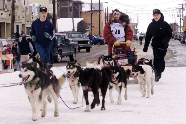FILE - In this March 17, 2000, file photo, Emmitt Peters, center, is followed by his sons Emmitt Jr., left, and Emory as he drives his team up the finish chute of the Iditarod Trail Sled Dog Race in Nome, Alaska. Alaska State Troopers confirm Peters, nicknamed the
