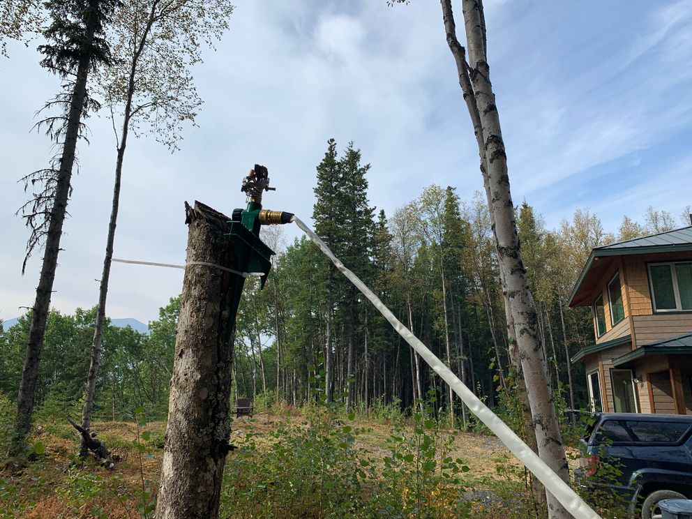 Firefighters have installed hose and sprinkler systems around homes near Cooper Landing as part of the fight against the Swan Lake fire, Friday, Aug. 30, 2019. (Jeff Parrott / ADN)