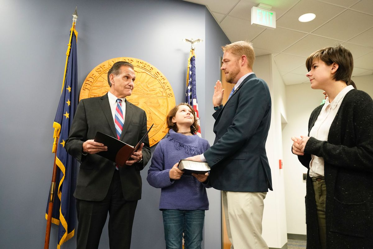 Sen. Josh Revak, R-Anchorage, is sworn in by Lt. Gov Kevin Meyer on Saturday, Nov. 2, 2019 at the Legislative Information Office in Anchorage. Revak, a former state representative, was nominated to fill a seat vacated by the death of Chris Birch. Revak's daughter Sydney Revak, 11, held the Bible as he was sworn in, and daughter Keilah Revak, 13, is pictured at right. (Loren Holmes / ADN)