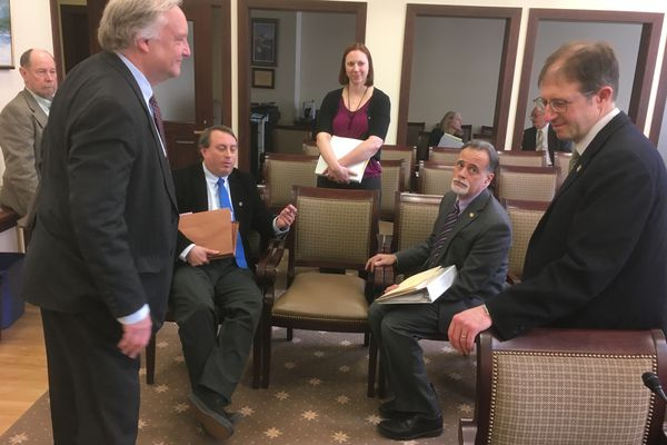 Sen. Peter Micciche, R-Soldotna (seated right) looks at Sen. Jesse Kiehl, D-Juneau (standing, right) as the two talk about Gov. Mike Dunleavy's proposed constitutional amendments with members of the governor's administration Monday, April 15, 2019. Also listening in is Assistant Attorney General Bill Milks (standing left), OMB policy director Mike Barnhill (sitting left), Cori Mills of the Alaska Department of Law (standing center) and Scott Ogan, former state senator and current legislative staffer (far left, leaning against the wall). (James Brooks / ADN)