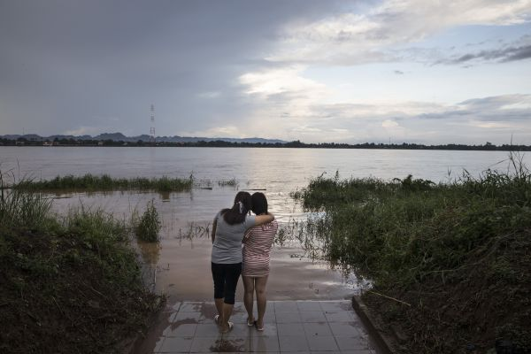 Two 23-year-old school friends from the border city of Hyesan, North Korea, look out at the Mekong River bordering Laos. The woman on the left had been sold to a Chinese man, a common fate for young North Korean women looking to make money for their families. Must credit: Photo by Paula Bronstein for The Washington Post