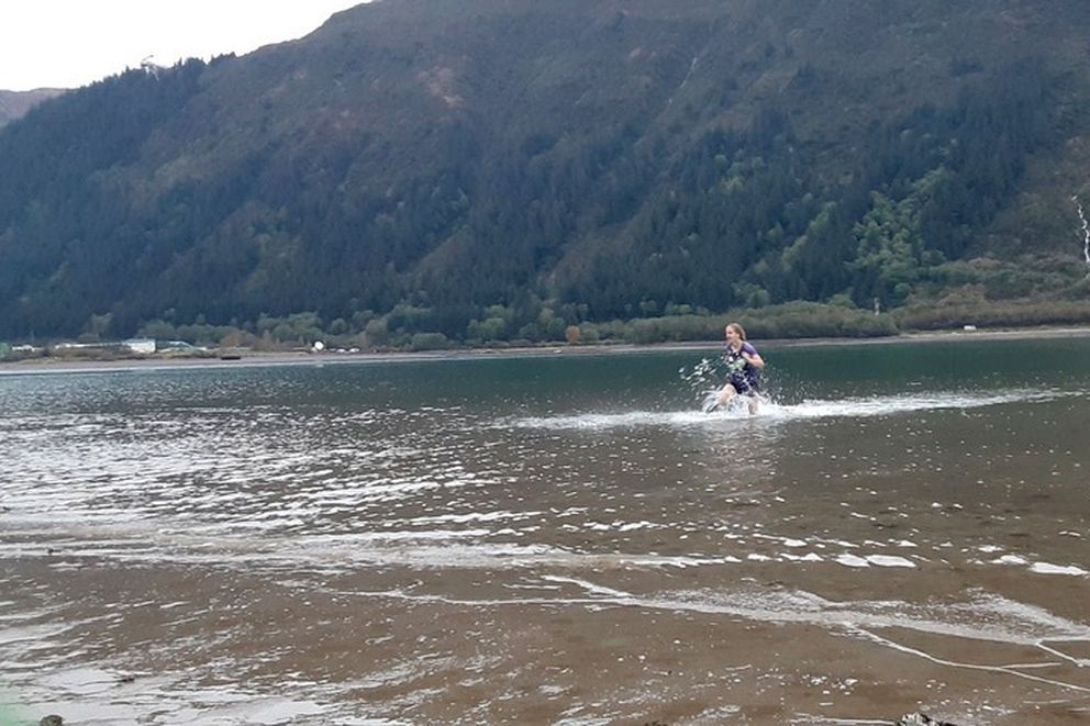 Freshman Mikayla Neal of Juneau-Douglas High School wades through the Gastineau Channel during a cross country relay race Tuesday in Juneau. (Photo by Abby Jahn)
