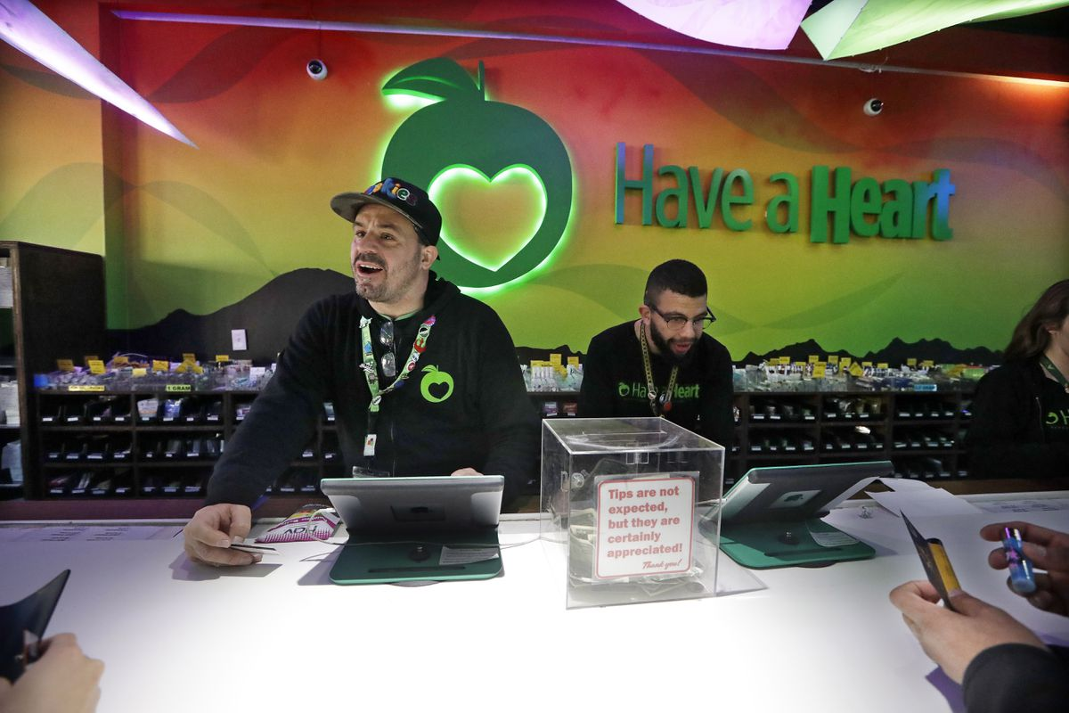 In this photo taken Thursday, March 28, 2019, employees Dan Giroux, left, and Dustin Barrington ring up sales for customers at a marijuana shop in Seattle. When Washington and Colorado launched their pioneering marijuana industries in the face of U.S. government prohibition, they imposed strict rules in hopes of keeping the U.S. Justice Department at bay. Five years later, federal authorities have stayed away, but the industry says it has been stifled by over-regulation. Lawmakers in both states have heard the complaints and are moving to ease the rules. (AP Photo/Elaine Thompson)