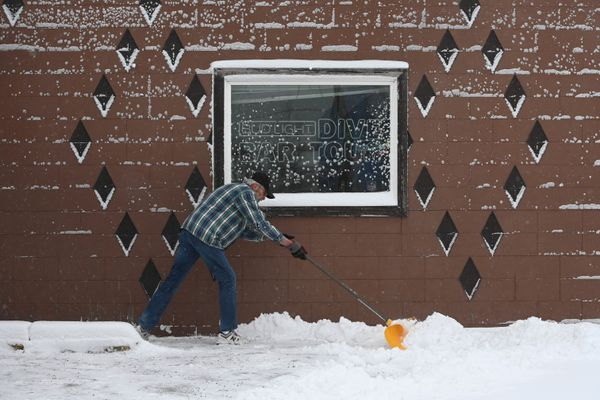 Howard Brown shovels snow away from the entrance to Van's Dive Bar on 5th Avenue on Wednesday, Feb. 12, 2020. More snow is in the forecast for Anchorage and Southcentral Alaska. (Bill Roth / ADN)