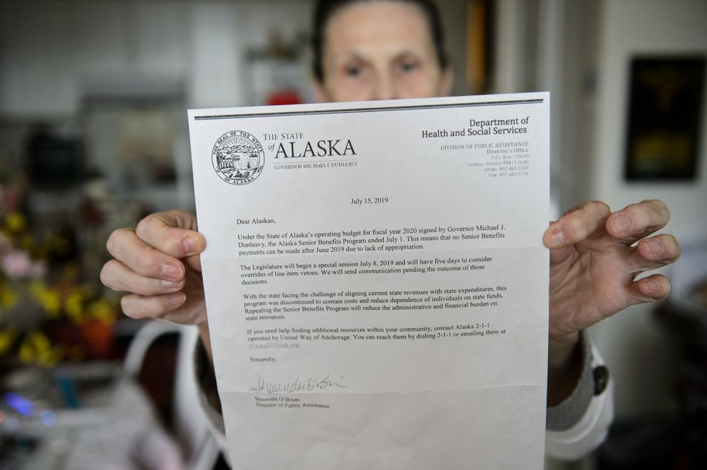 Barbara May, 78 of Anchorage, holds a letter from the Alaska Department of Health and Social Services notifying her that the Alaska Senior Benefits Payment Program had ended. (Marc Lester / ADN)