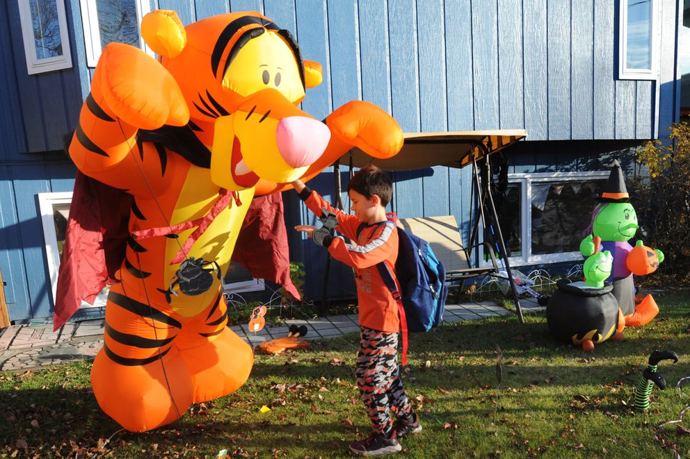 Magnus Shipe, 9, stands up a Halloween decoration that fell over in the wind in the Turnagain Heights subdivision on Wednesday, Oct. 30, 2019. (Bill Roth / ADN)