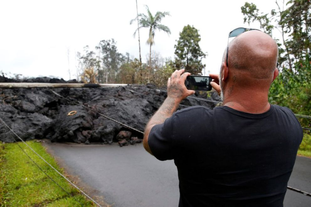 A resident of the Leilani Estates subdivision takes photos of a lava flow near his home. REUTERS/ Terray Sylvester