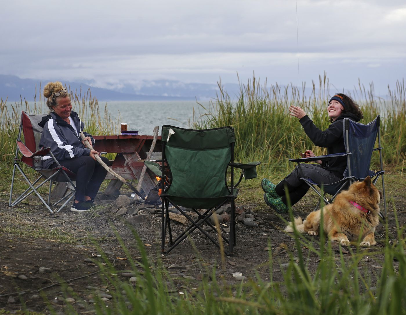 Abigail Schneiders, right, flies a kite as she sits with Donna Schneiders, left, and their dog, Elka, on a beach along the Homer Spit on Aug. 8, 2020. (Emily Mesner / ADN)