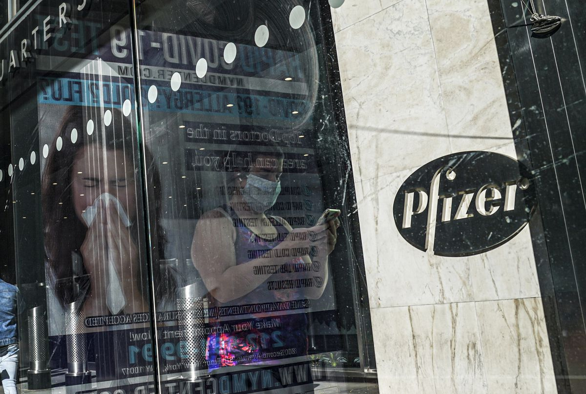 An ad for COVID-19 testing reflects on glass at a bus stop, as pedestrians walk past Pfizer world headquarters in New York. (AP Photo/Bebeto Matthews, File)