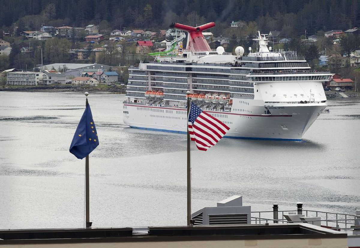 The Carnival Spirit cruise ship is seen through the national and state flag on top of the Alaska Capitol as the first ship of the season enters Juneau's downtown harbor on Thursday, May 3, 2012. (AP Photo/Michael Penn, Juneau Empire)