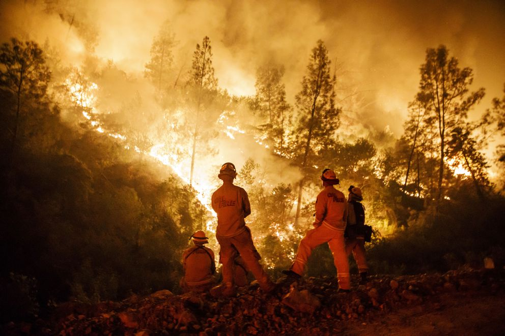 Firefighters monitor a burn operation on top of a ridge near the town of Ladoga, Calif., on August 7, 2018. (Marcus Yam/Los Angeles Times/TNS)