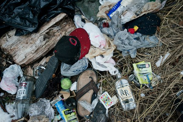 Garbage left at a vacated homeless camp in the woods along the Campbell Creek greenbelt show several liquor bottles and items of clothing. Photographed on Friday, November 7, 2014. Marc Lester / ADN