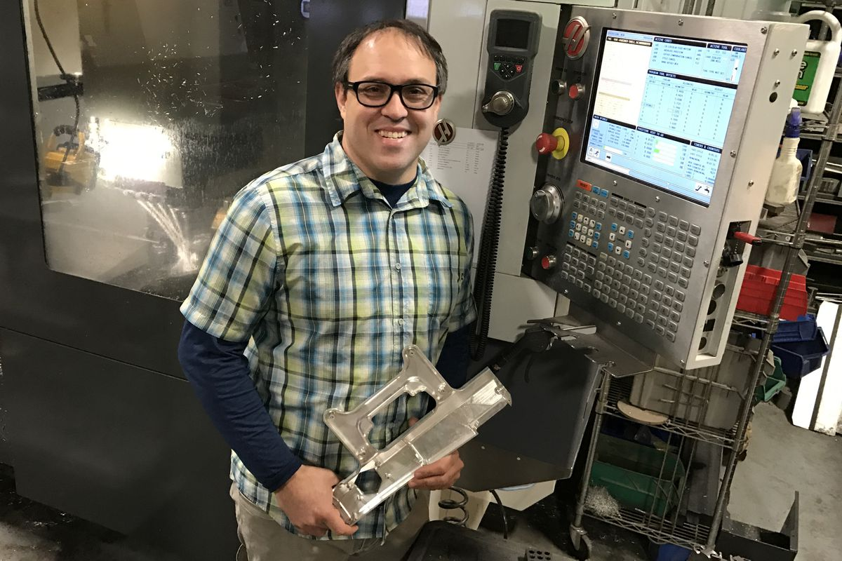 Hans Vogel, president of Triverus, stands in front of a computerized milling machine Monday. (Charles Wohlforth / Alaska Dispatch News)