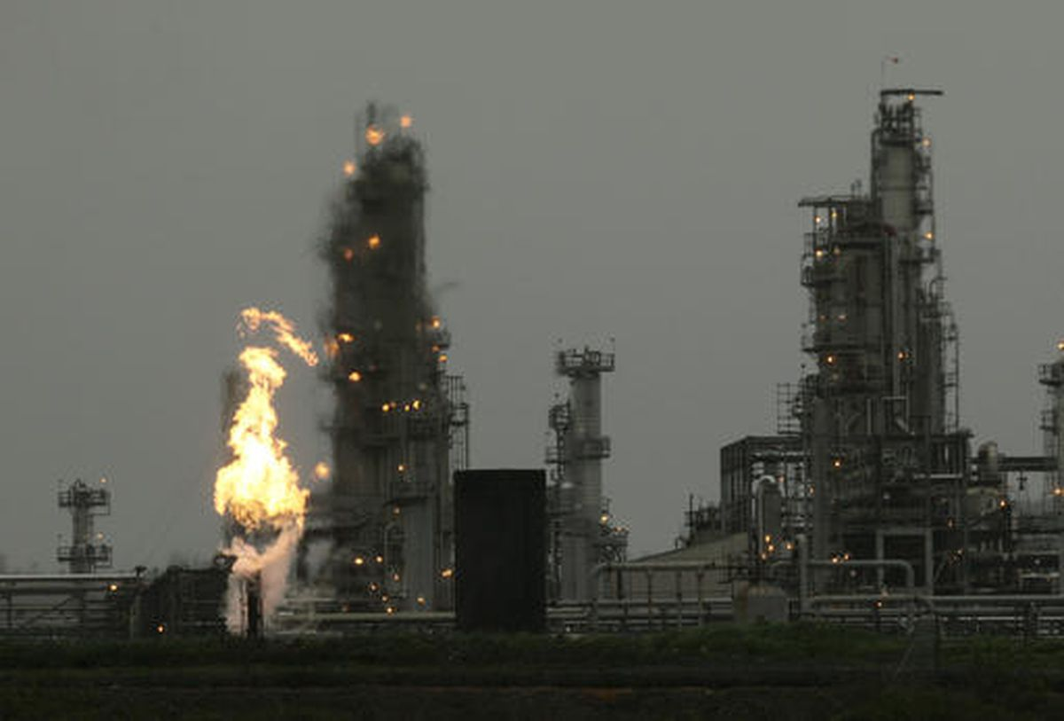 In this 2010 photo, a Tesoro Corp. refinery, including a gas flare flame that is part of normal plant of operations, is shown in Anacortes, Wash. (AP Photo/Ted S. Warren)