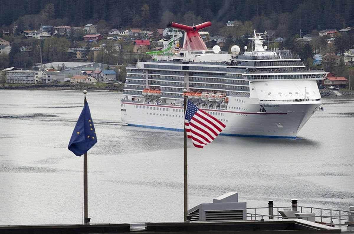 The Carnival Spirit cruise ship is seen beyond flags on top of the Alaska Capitol on May 3, 2012. (ADN file photo)