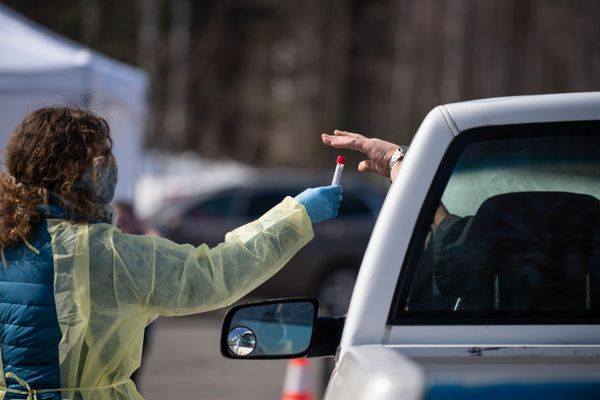 Mat-Su public health nurse Karrin Parker receives a COVID-19 test sample from a patient at a drive-through test site at Su Valley Jr/Sr High School in Talkeetna on Thursday, April 30, 2020. (Loren Holmes / ADN)