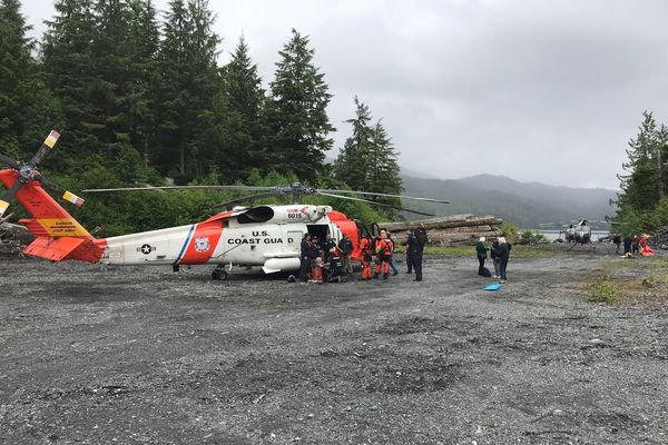 A Coast Guard Air Station Sitka MH-60 Jayhawk helicopter aircrew and Ketchikan Volunteer Rescue Squad personnel tend to survivors from a downed aircraft on Mount Jumbo on Prince of Wales Island, Alaska, July 10, 2018. All 11 people aboard the aircraft survived and were hoisted by a Jayhawk helicopter aircrew and taken to emergency medical personnel for triage before being further taken to Ketchikan for higher level medical care. (U.S. Coast Guard photo)