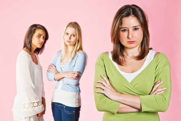 Three attractive young women looking worried and annoyed against a pink background. The two women in the background seem to disapprove of the angry-looking girl in the foreground. (Getty)