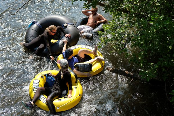 Tubers help each other avoid a brushy bank of Campbell Creek. A stretch of Campbell Creek west of Lake Otis Parkway attracted many floaters and tubers looking to cool off on warm Saturday afternoon on June 29, 2019. (Marc Lester / ADN)