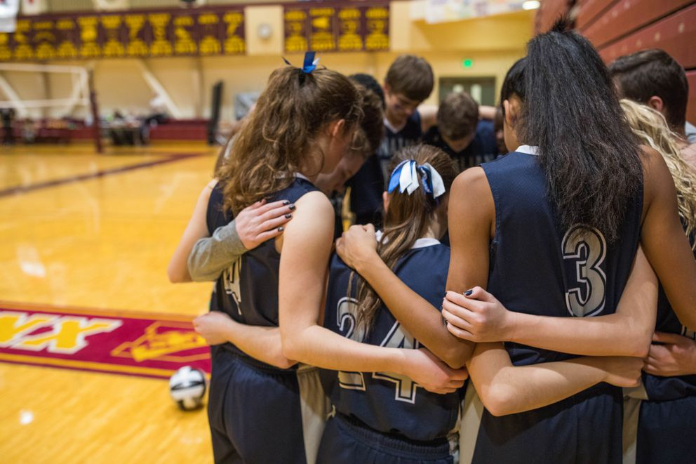 The Tanalian Lynx pray before a volleyball match against Hoonah on Saturday at Dimond High School. (Loren Holmes / Alaska Dispatch News)