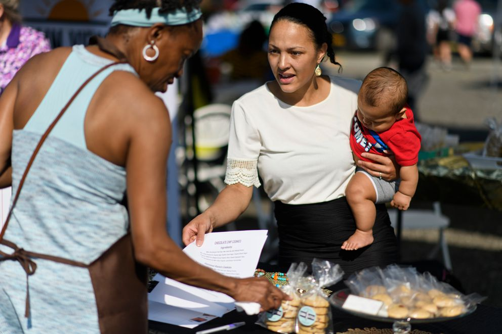 Shimei Good, right, holds six-month-old Giosiah Good while she talks to a customer at her jewelry and gluten-free baked goods stand at Grow North Farm's monthly market. (Marc Lester / ADN)