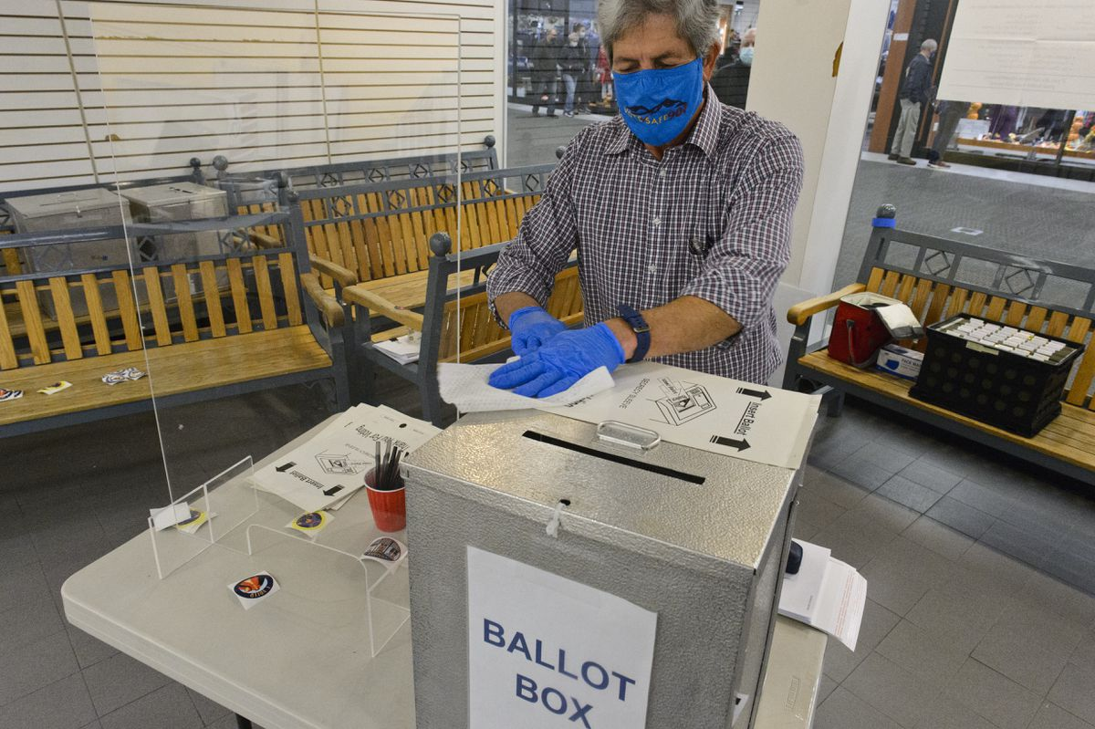 Election worker Chris Kilvay wipes down secrecy sleeves after ballots are slipped into the the collection box at the Midtown Mall on Monday, October 19, 2020. (Marc Lester / ADN)