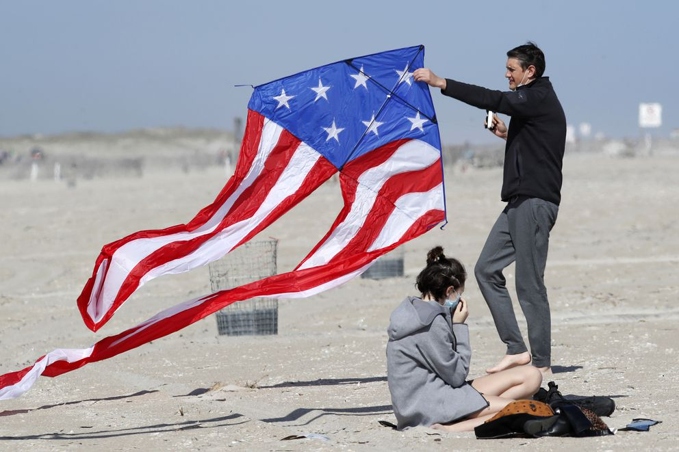 Stephen Wilmer, of Lindenhurst, N.Y., works at getting his kite aloft in the breeze as his daughter Emma adjusts her protective face mask as the family visited Jones Beach, in Wantagh, N.Y., Thursday, May 21, 2020, amid the coronavirus pandemic. As pandemic lockdowns ease across the United States, millions of Americans are set to take tentative steps outdoors to celebrate Memorial Day, the traditional start of summer. But public health officials are concerned that if people congregate in crowds or engage in other risky behaviors, the long weekend could cause the coronavirus to come roaring back. (AP Photo/Kathy Willens)