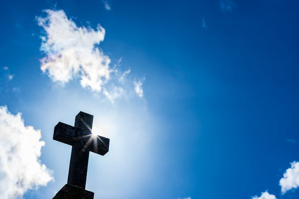 Silhouette of cross shape with sunrays and cloudy sky.