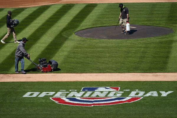 Grounds crew members prepare the surface for the Colorado Rockies to host the Los Angeles Dodgers in the teams' regular-season opening game Wednesday, March 31, 2021, at the stadium in downtown Denver. A small number of fans were allowed to watch the Rockies go through a workout Wednesday before the team hosts the Dodgers on Thursday. (AP Photo/David Zalubowski)