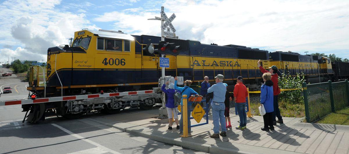 Tourists wave as an empty Alaska Railroad gravel train heads back to Mat-Su for more cargo on Monday afternoon, June 20, 2016, at Ship Creek. (Erik Hill / ADN)
