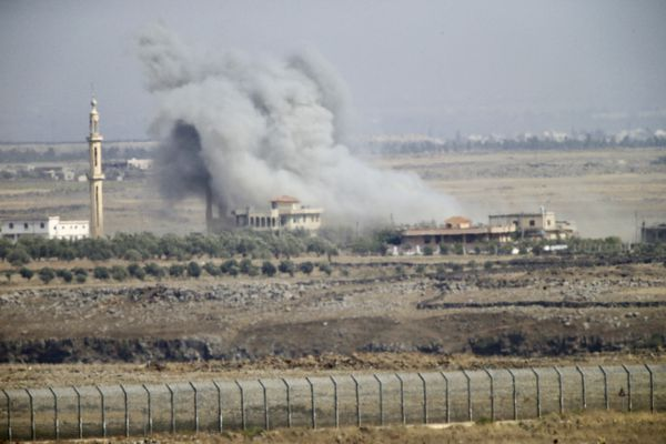 Smoke and explosions from the fighting between forces loyal to Syrian President Bashar Assad and rebels in the Darra province can be seen from the Israeli-controlled Golan Heights, Wednesday, July 25, 2018. (AP Photo/Ariel Schalit)
