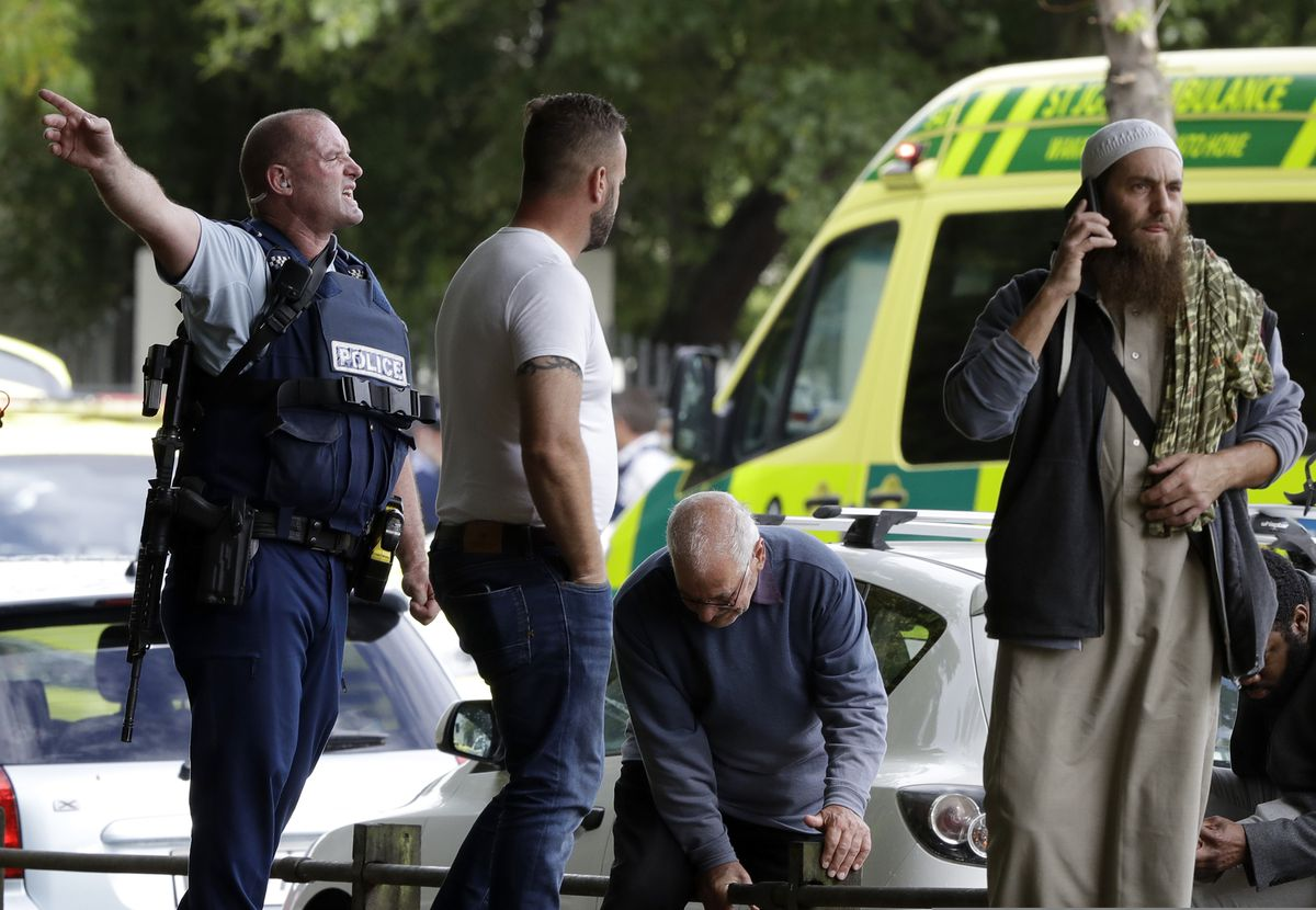 Police attempt to clear people from outside a mosque in central Christchurch, New Zealand, Friday, March 15, 2019, after a mass shooting. (AP Photo/Mark Baker)