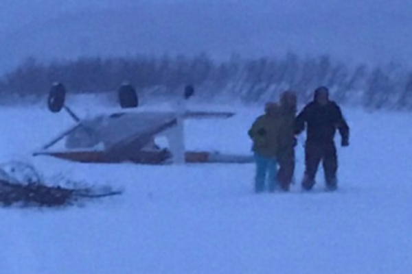 Three people walk away after their Cessna 180 crashed in the woods about 57 miles west of Anchorage, Alaska, Jan. 30, 2017. A Coast Guard Air Station Kodiak MH-60T Jayhawk crew transported the three to Anchorage International Airport. U.S. Coast Guard photo by Petty Officer 1st Class William Colclough .