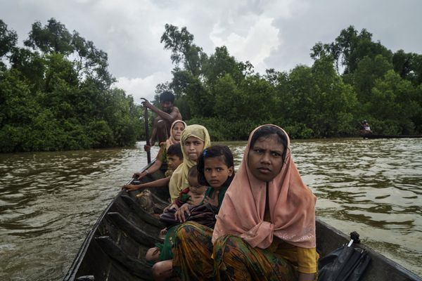Tasmida, front, an 18-year-old Rohingya refugee who spent eight days walking and hiding to reach the border, leaves Myanmar by crossing the Naf River near Palong Khali, Bangladesh, Sept. 4, 2017. The Rohingya, a Muslim ethnic group, have faced violence and discrimination in Myanmar for decades, but are now fleeing the majority-Buddhist country in unprecedented numbers. (Adam Dean/The New York Times)