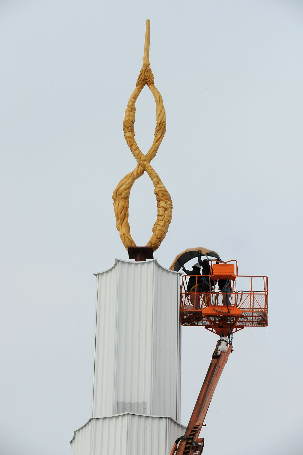 Pastor Isaac Aguirre, Miguel Mejivar and Naason Aguirre install the first section of the dome between the top section of the Iglesia La Luz Del Mundo church and the spire on March 15. The church is scheduled to be completed in the fall. (Bob Hallinen / ADN)