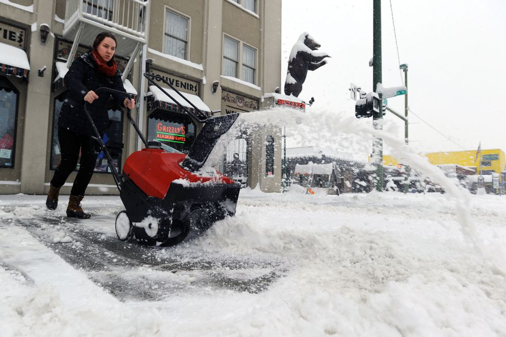 Brionna Strange clears snow from the sidewalk in front of Grizzly's Gifts on Wednesday morning, March 29, 2017, along West Fourth Avenue downtown. (Erik Hill / Alaska Dispatch News)