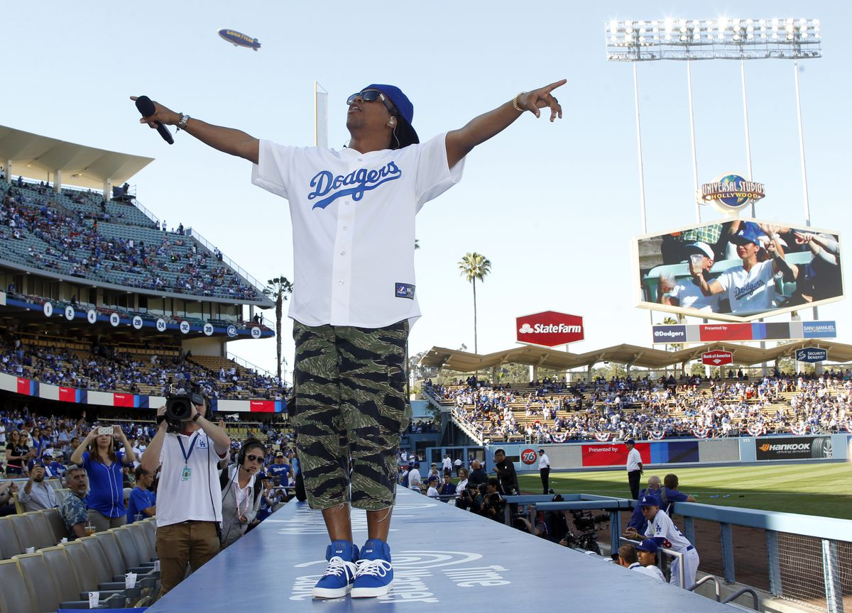 Lupe Fiasco performs on the top of the dugout prior to a baseball game between the San Francisco Giants and the Los Angeles Dodgers on Sunday, April 6, 2014, in Los Angeles. (AP Photo/Alex Gallardo)