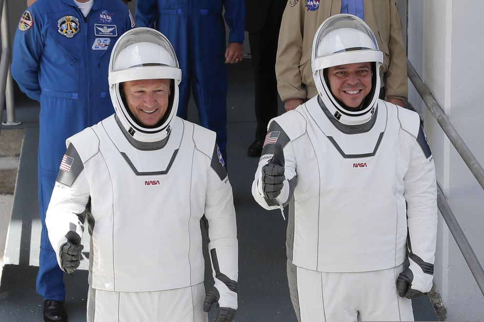 FILE- In this May, 30, 2020 file photo, NASA astronauts Douglas Hurley, left, and Robert Behnken walk out of the Neil A. Armstrong Operations and Checkout Building on their way to Pad 39-A, at the Kennedy Space Center in Cape Canaveral, Fla. Behnken and Hurley riding the Dragon SpaceX capsule are headed toward a splashdown Sunday, Aug. 2, 2020, in the Gulf of Mexico to close out their two-month test flight. It will mark the first splashdown in 45 years for NASA astronauts and the first return in the gulf. Unlike Florida's Atlantic coast, already feeling the effects of Tropical Storm Isaias, the waves and wind were calm near Pensacola in the Florida Panhandle. (AP Photo/John Raoux, File)