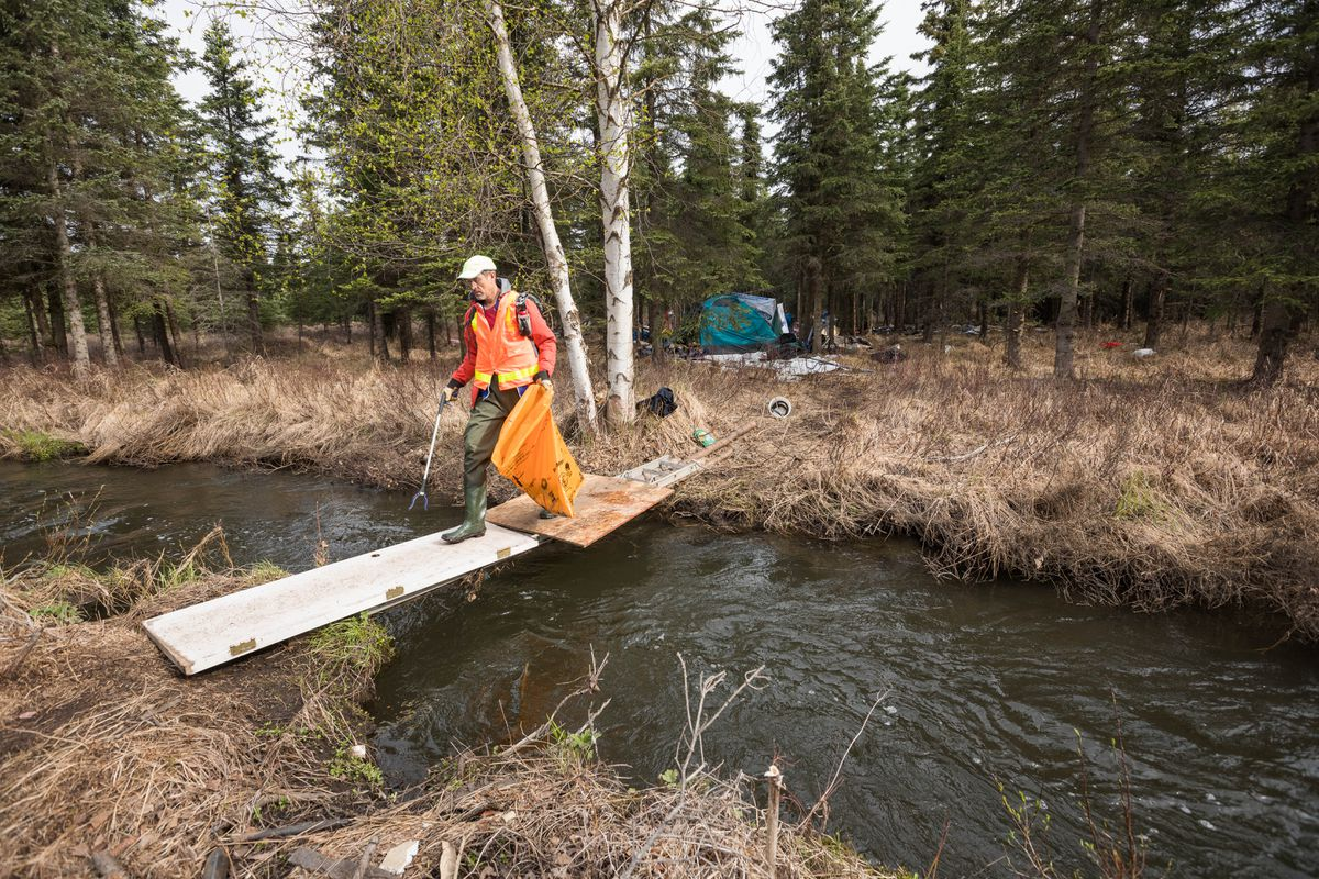 David Evans crosses a makeshift bridge over Chester Creek near a homeless camp on Saturday, May 11, 2019 during the annual citywide creek cleanup event. The effort was organized in 1984 by then-mayor Tony Knowles, according to the Anchorage Waterways Council. (Loren Holmes / ADN)
