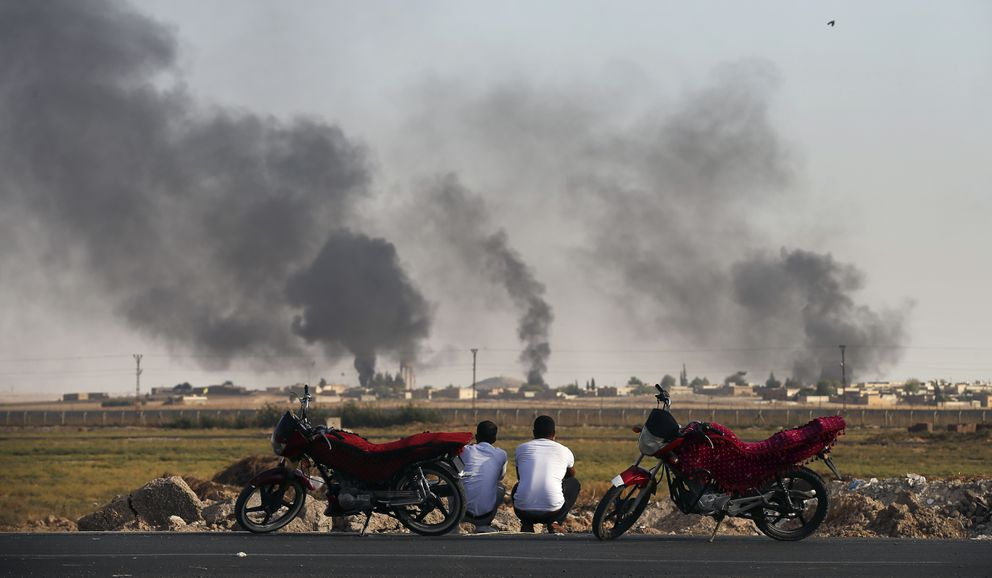 People in Akcakale Sanliurfa province, southeastern Turkey, at the border with Syria, watch smoke billowing inside Syria, during bombardment by Turkish forces, Thursday, Oct. 10, 2019. Turkey's foreign minister says Turkish troops intend to move some 30 kilometers (19 miles) deep into northern Syria and that its operation will last until all 'terrorists are neutralized, ' a reference to Syrian Kurdish fighters. (AP Photo/Emrah Gurel)